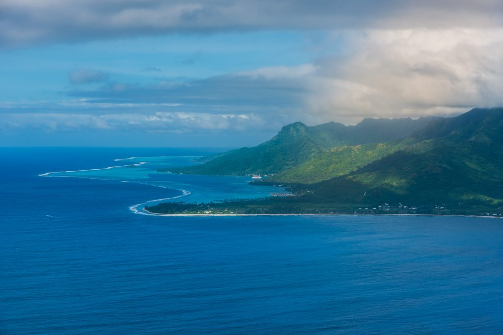 The green island of Moorea surrounded with a bluer ocean, French-Polynesia
