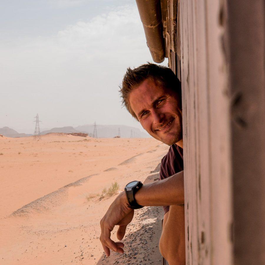 Gerben van der Waals, travel photographer, hanging out of the window of a train, Jordan